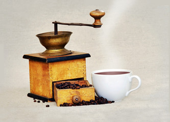 coffee mill and cup of hot black coffee
