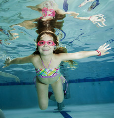 Happy little girl underwater in swimming pool
