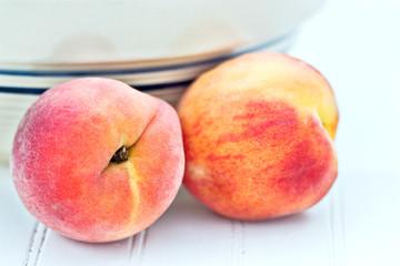 Fresh peaches by an antique bowl