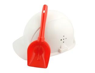 White hard hat and kid's shovel isolated