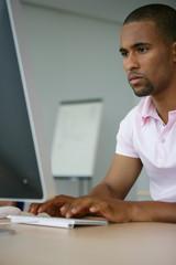 Jeune homme métis assis devant un ordinateur