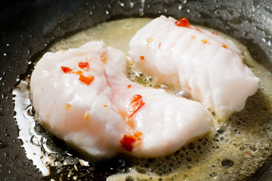 monk fish with chilies cooking in work