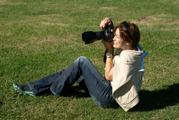 professional woman photographer in park on a gras