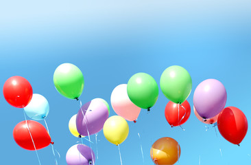 Many multi-colored balloons on a background of the blue sky