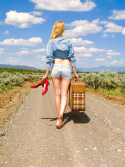 Girl walking on a dirt road with a suitcase