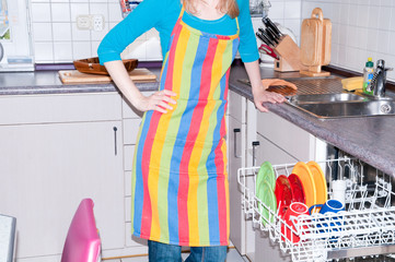 Frau räumt Geschirrspüler aus
