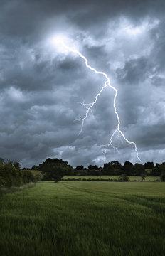 Lightening strike over field landscape