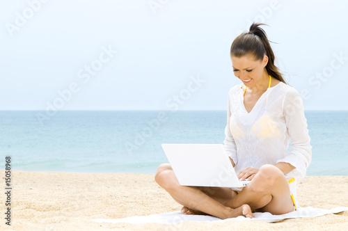 dfc10aac576e Hübsche Frau sitzt mit Laptop am Strand
