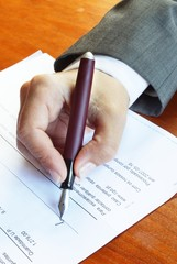 Woman in a suit signing a document