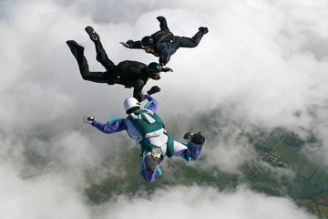 Three skydivers in freefall holding hands
