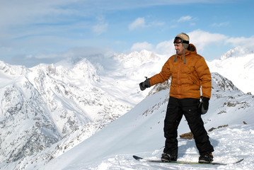 snowboarder costs at top of mountain and shows a hand