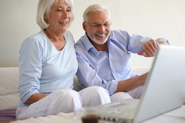 Couple de seniors souriants connectés à une webcam