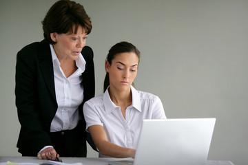 Femme senior souriante près d'une femme devant un ordinateur