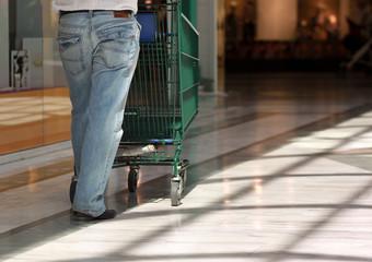 homme poussant son caddie dans le centre commercial