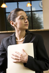 Young female office worker holding folder