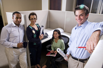 Business colleagues meeting in an office cubicle