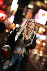 Beautiful blond woman in fur coat in night city