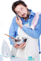 Man cooking, ironing and speaking on phone