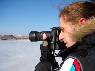 man takes pictures the frozen sea in winter