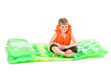 Boy sitting on beach mattress