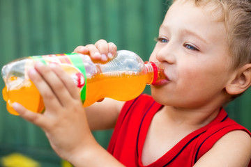 Boy drinking unhealthy bottled soda