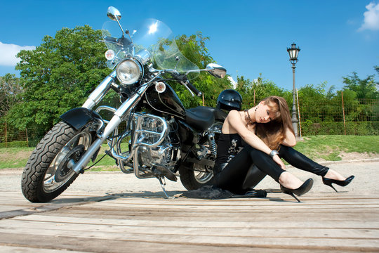 A pretty woman siting  near by motorbike