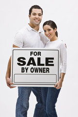 Couple With For Sale By Owner Sign