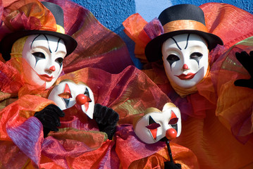 Two clowns with mask in the hands