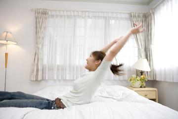 ベッド上ではしゃぐ女性