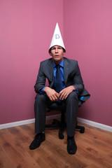 Businessman sat in corner wearing a dunce hat