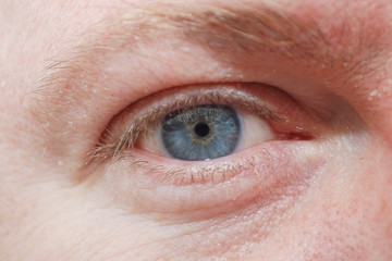 Man's blue eye closeup.