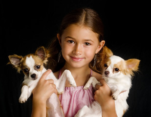 Girl holding two pet Chihuahua's