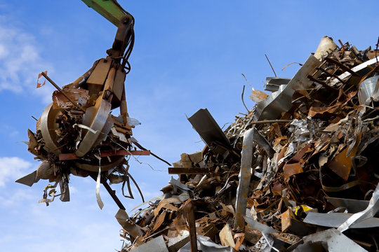 crane grabber loading a rusty metal