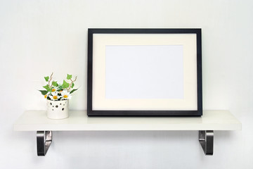 Potted sunflowers and photo frame on white shelf.