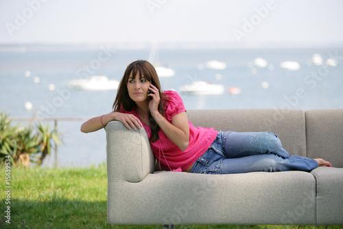 femme assise sur un canap t l phonant avec t l phone portable photo libre de droits sur la. Black Bedroom Furniture Sets. Home Design Ideas