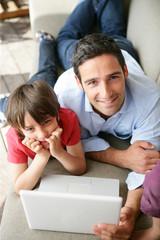 homme et garçon étendus sur un canapé devant un ordinateur