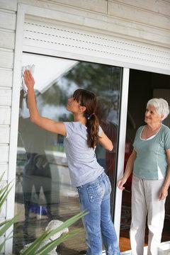 Femme nettoyant une baie vitrée près d'une femme senior