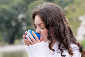 Portrait of the young woman drinking hot tea outdoors