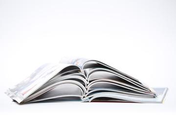 pile of colorful opened magazines on white background