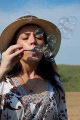 beautiful girl making soap bubbles