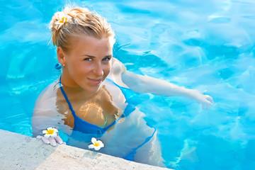 Blonde girl relaxing in hotel pool