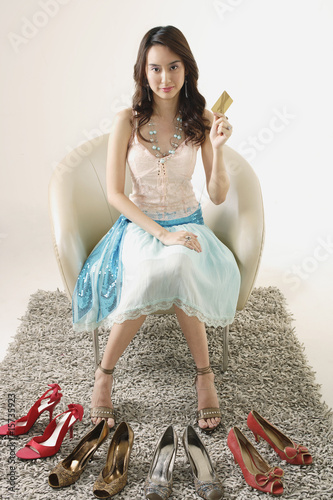 46cd831d85 Woman holding credit card behind four pairs of shoes