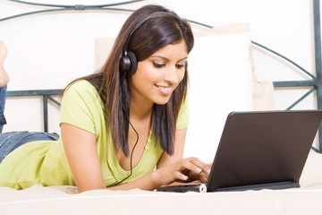 arabian woman listening music on bed with laptop