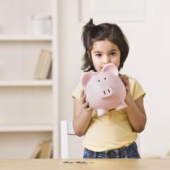 Little Girl Holding a Piggy Bank