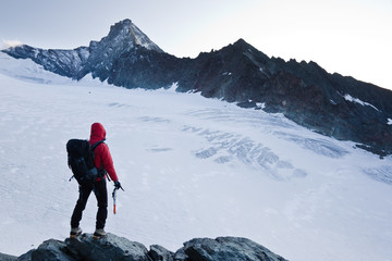 Climber stands in front of a big glacier
