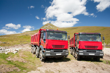 Two large red dump trucks