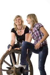 Mother and daughter with old car-wheel