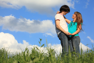young pair holds each other in  grass against sky