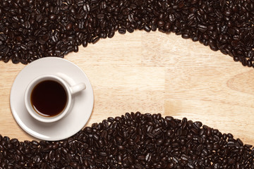 Dark Roasted Coffee Beans and Cup on Wood Background