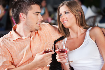 couple outdoor drinking red wine on summer evening